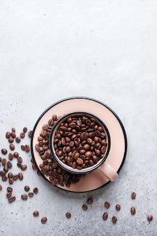 灰色のコンクリートの上にコーヒー豆が入ったカップ