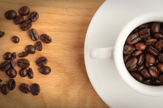 A cup with coffee and coffee beans on wood background