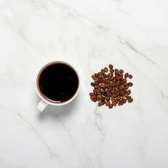 Cup with coffee and coffee grains on a marble table. square. concept breakfast, black coffee, coffee for the night, insomnia. flat lay, top view