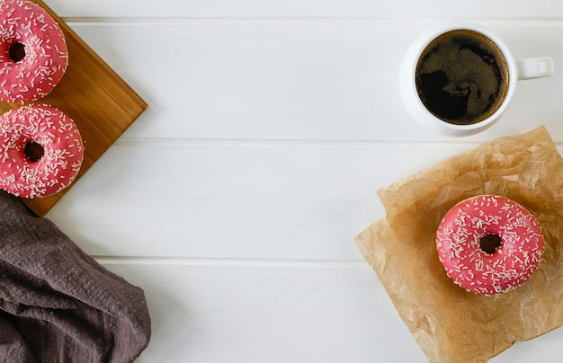 Cup with coffee and donuts on a white wooden table