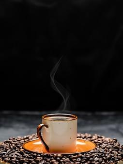 暗いテーブルに配置されたコーヒーエスプレッソとカップ。ローストコーヒー豆は一杯のコーヒーの周りにあります。クローズアップ、選択的な焦点