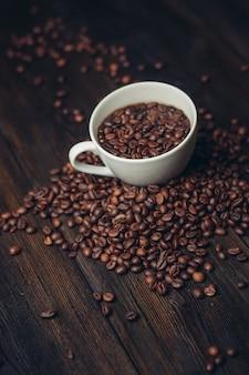 木製のテーブルにコーヒーの粒が入ったカップアロマドリンクアラビカ製品