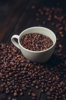 木製のテーブルにコーヒーの粒が入ったカップアロマドリンクアラビカ製品。