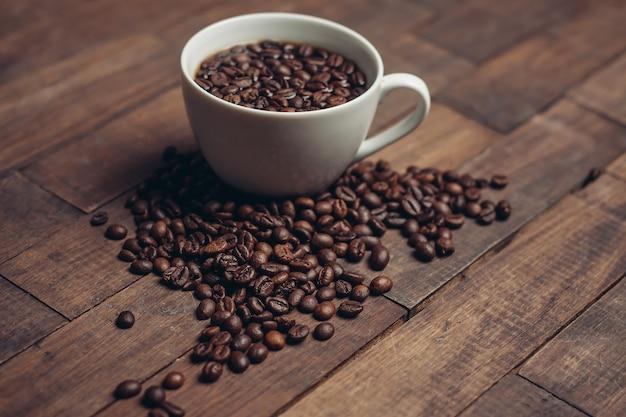 木製のテーブルにコーヒーの粒が入ったカップアロマドリンク