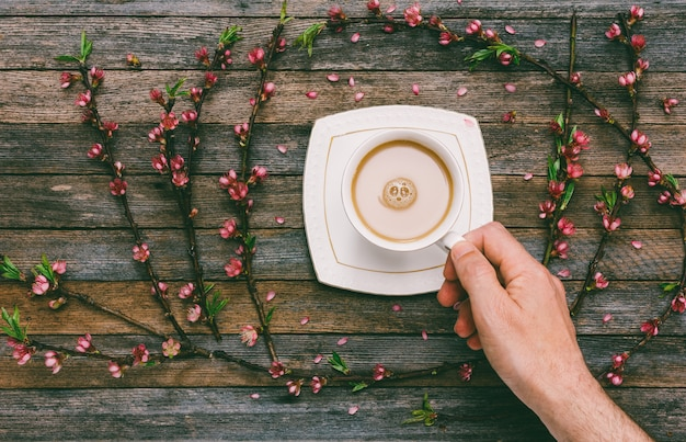 Cup with coffee milk in a male hand on a  of an old wooden table with peach branches with pink flowers, top view