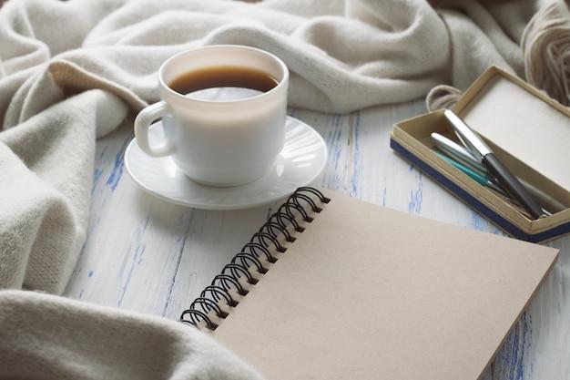 커피, 메모장, 흰색 나무 테이블에 펜 컵. 봄의 개념