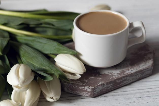 흰색 튤립 가운데 흰색 나무 테이블에 커피 컵