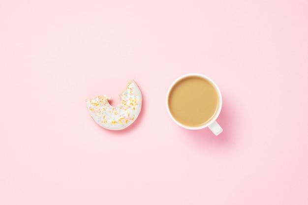 Чашка с кофе или чаем. укушенный свежий вкусный сладкий пончик на розовом фоне. добавлен текст доброе утро. концепция пекарня, свежая выпечка, вкусный завтрак, фаст-фуд, кафе. плоская планировка, вид сверху.