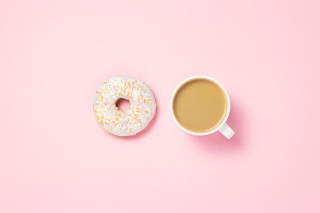 コーヒーまたは紅茶のカップ。ピンクの背景に新鮮なおいしい甘いドーナツ。パン屋さんのコンセプト、焼きたてのペストリー、おいしい朝食、ファーストフード、コーヒーショップ。