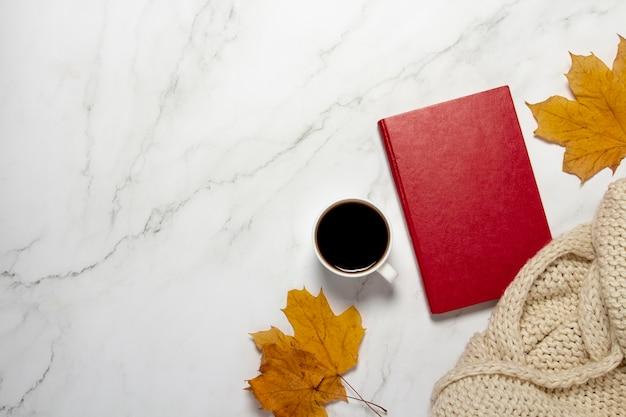 Чашка с кофе или чаем, желтые осенние листья и книга на мраморном столе