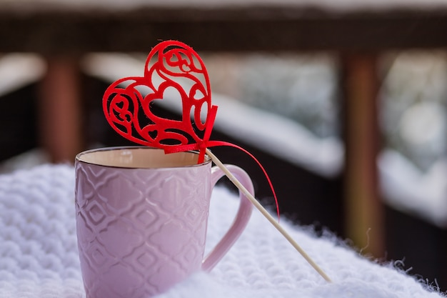 Cup with coffee and red heart on white scarf on balcony background. good morning alps, mountains.