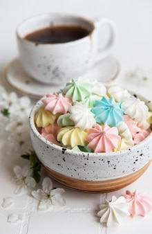 Cup with coffee and small meringues in the bowl  on a tiled background