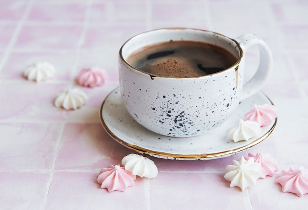 Cup with coffee and small meringues on a tiled background