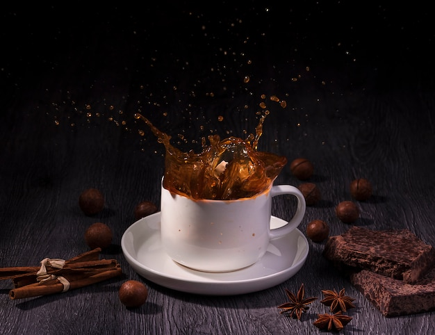 A cup with coffee splash with nuts and cinnamon stick on table wood over dark background