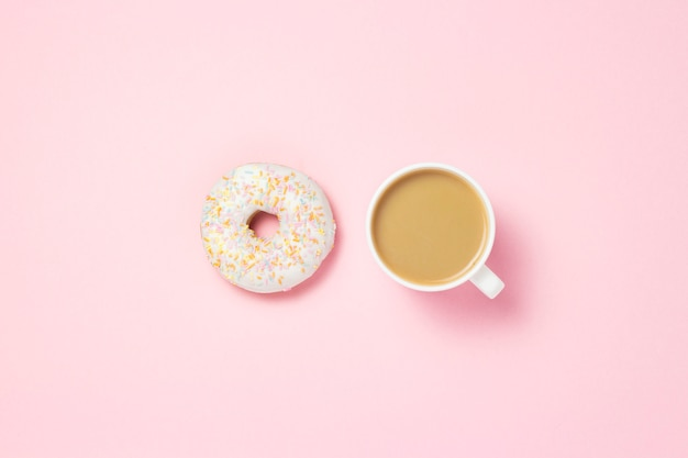 Cup with coffee or tea. fresh tasty sweet donut on a pink background. bakery concept, fresh pastries, delicious breakfast, fast food, coffee shop.