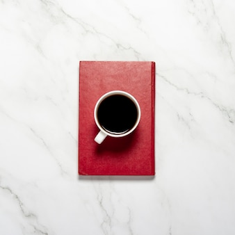 Cup with coffee or tea and a red book on a marble table. concept of breakfast, education, knowledge, reading books. flat lay, top view