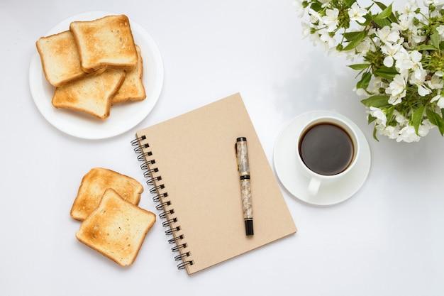 コーヒー、白い皿にトースト、メモ帳、白に花のついた枝とカップ。健康的な春の朝食の概念