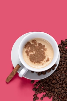 Cup with coffee with milk and some coffee beans isolated pink background