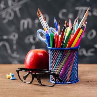 Cup with colourful stationery near glasses and apple on table