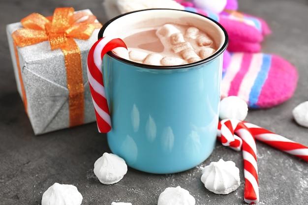 회색 배경에 맛있는 코코아 음료와 마시멜로가 있는 컵. 크리스마스 컨셉