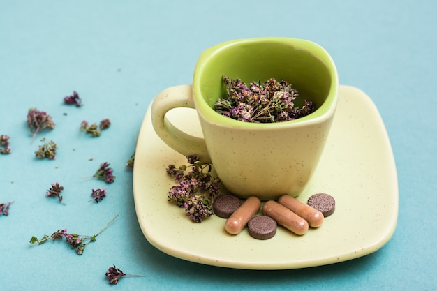 A cup with dried oregano and herbal medicinal capsules and pills on a saucer on a green table. alternative medicine