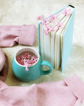 Cup with a drink, fresh flowers bookmarks in an open book, woolen pink sweater on a light table