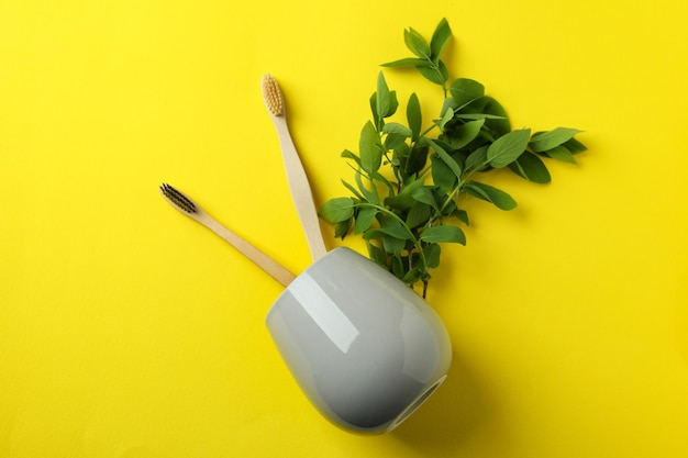 Cup with eco friendly toothbrushes and twigs on yellow background