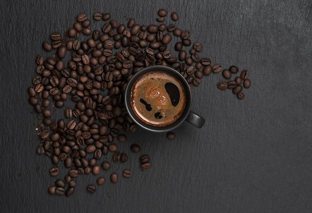 Чашка с эспрессо, вокруг чашки кофе в зернах