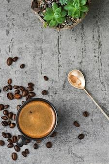 Чашка с кофе эспрессо и кофейными зернами на сером каменном столе.