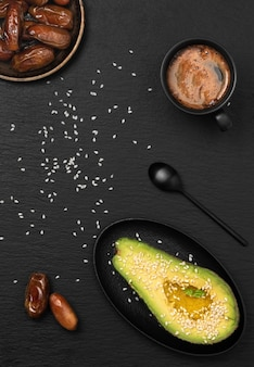 Cup with espresso nearby half avocado with olive oil and sesame seeds and dried dates