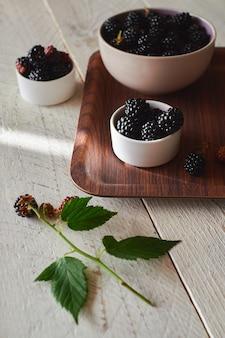 茶色のトレイに新鮮な黒と赤のブラックベリーが入ったカップ、緑のブラックベリーの葉がテーブルの上にあります。明るい木の背景