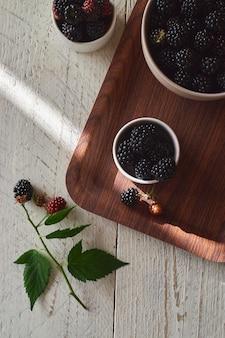 茶色のトレイに新鮮な黒と赤のブラックベリーが入ったカップ、緑のブラックベリーの葉がテーブルの上にあります。