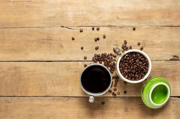 淹れたてのコーヒーのカップとコーヒーの穀物が入った缶、コーヒー豆が木製のテーブルに散らばっています。バナー。コーヒーのコンセプト、プランテーション、加工、コレクション