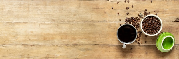 Cup with fresh coffee and a can with coffee grains, coffee beans are scattered on a wooden table.
