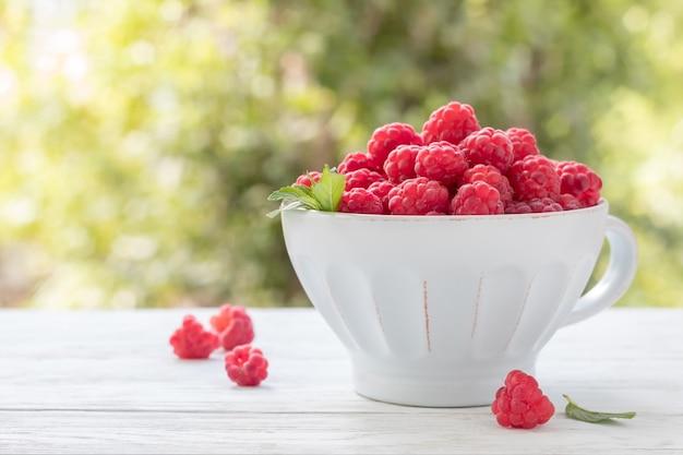 Чашка со свежей спелой малиной на белом деревянном столе на открытом воздухе, копией пространства. вкусные летние фрукты