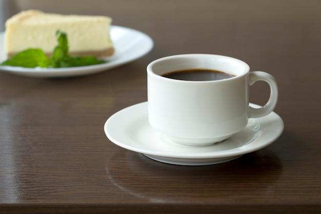 Чашка со свежесваренным кофе и ломтик чизкейка на столе в кафе.