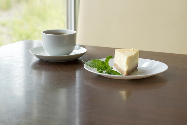 Cup with freshly brewed coffee and a slice of cheesecake on the table in a cafe.