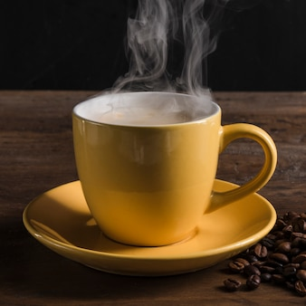 Cup with hot beverage near coffee beans