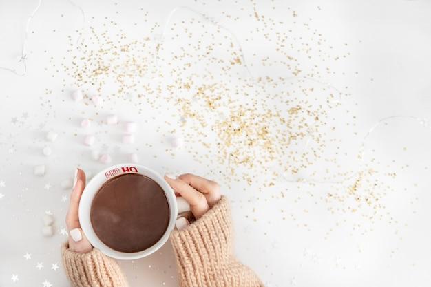 Чашка с горячим шоколадом в руках на белом с блестящими звездами и герландом