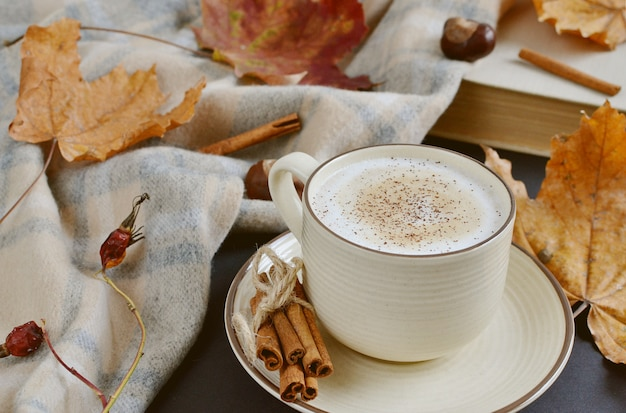 Cup with hot coffee cappuccino autumn time yellow leaves chestnuts