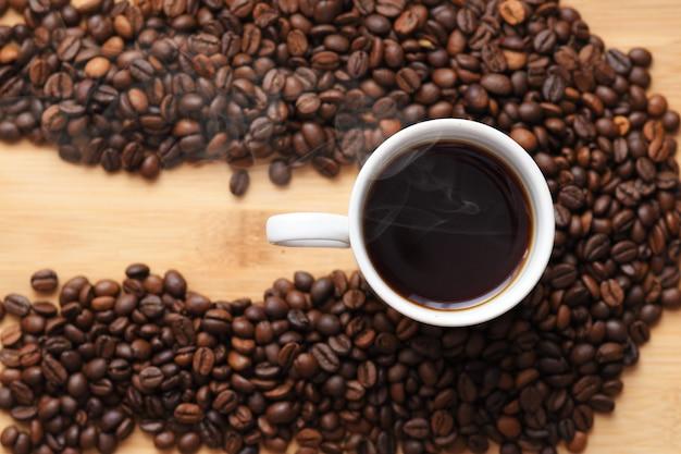 コーヒー豆に囲まれたホットコーヒーのカップ