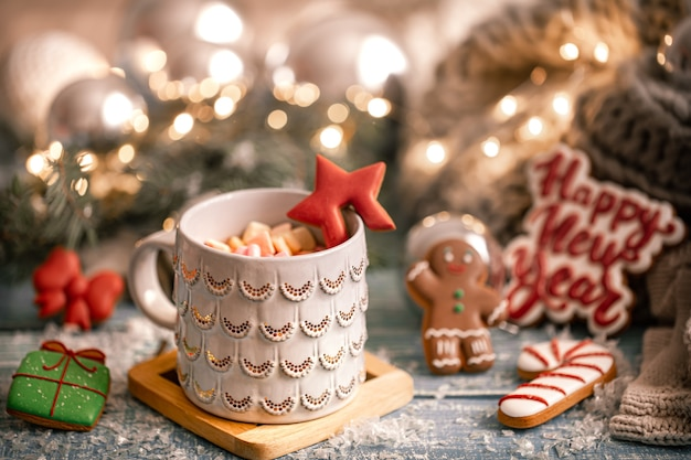 Cup with a hot drink, marshmallow on a table with christmas decorations on background with gingerbread cookies. new year concept.
