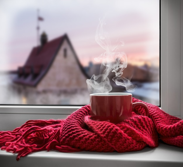 Cup with a hot drink on the windowsill