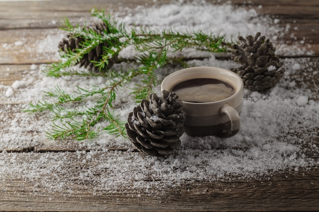 Cup with hot drink over winter wooden table
