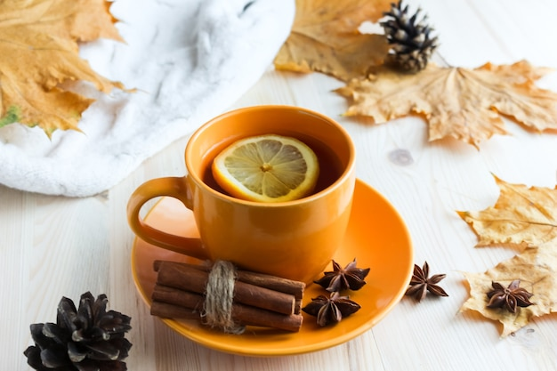 Cup with hot tea and lemon, autumn leaves on wooden table