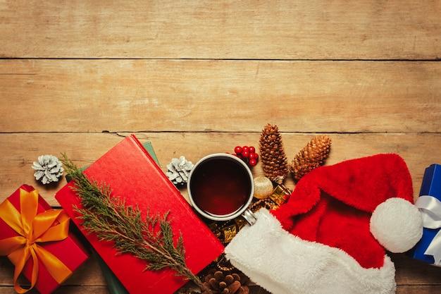 Чашка с горячим чаем, шляпу санта-клауса, подарок, рождественские украшения, книги на деревянном фоне. рождество, зимние каникулы. плоская планировка, вид сверху