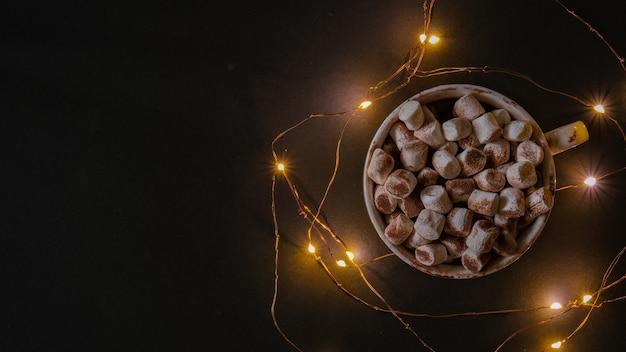 Чашка с горячим зимним какао и зефиром на ночь. рождественские огни гирлянды. спокойной ночи, сладких снов. уютные зимние дни. хюгге.