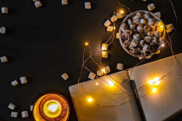 Чашка с горячим зимним какао и зефиром ночью рождественские огни чайные свечи спокойной ночи св ...