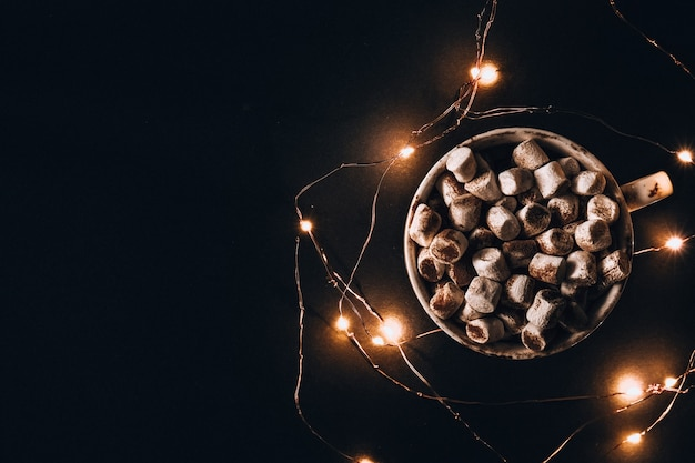Cup with hot winter cacao and marshmallows at night. christmas garland lights. good night sweet dreams. cozy winter days. hygge.