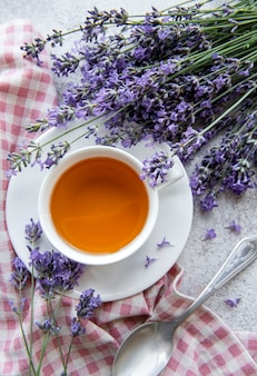 Cup with lavender tea and fresh lavender flowers